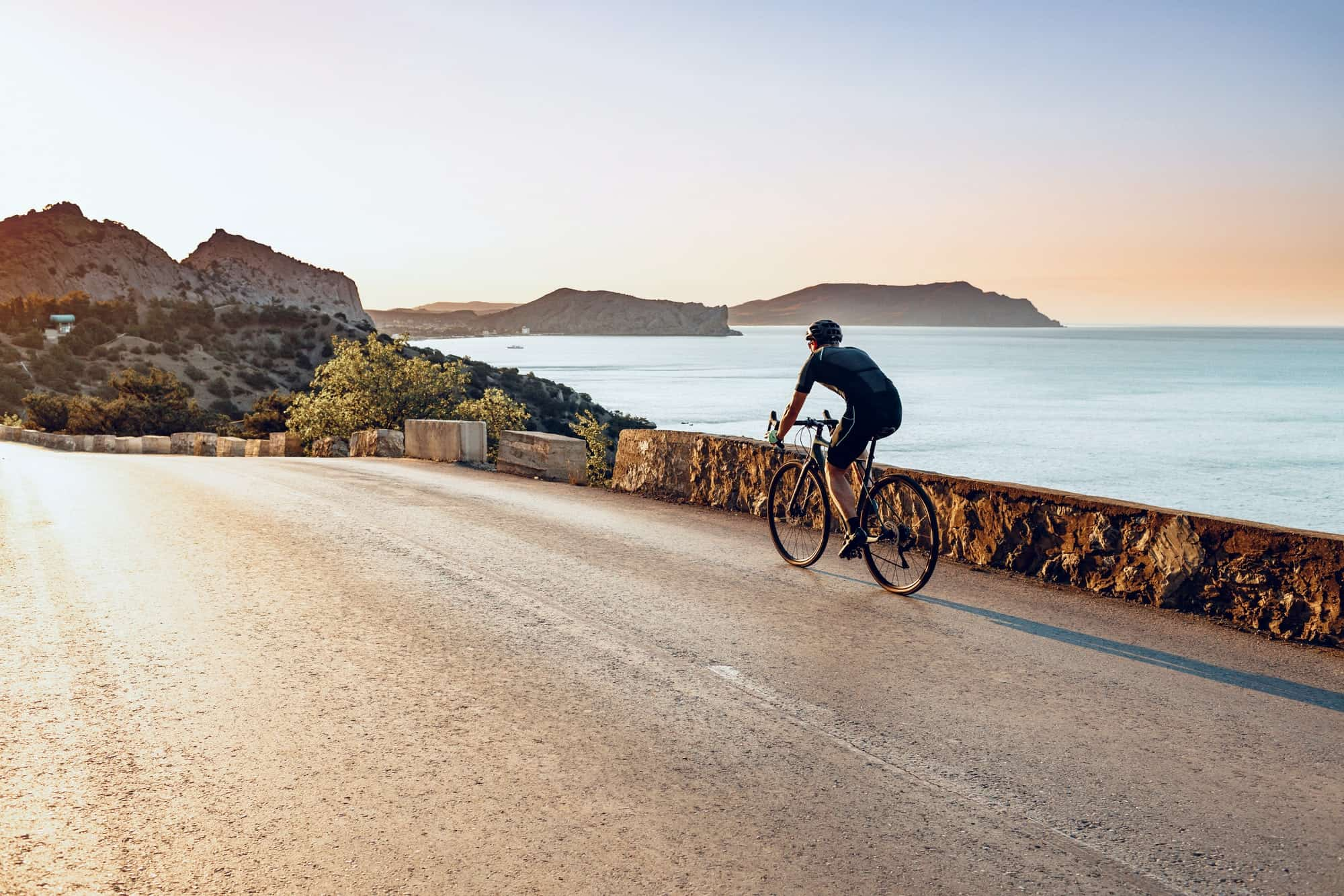 Cycling sport athlete man riding on coastal road